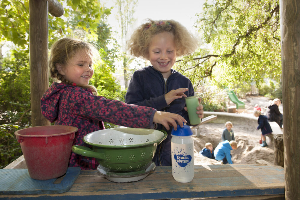 Kinderen pakken drinkwater tijdens buitenspelen