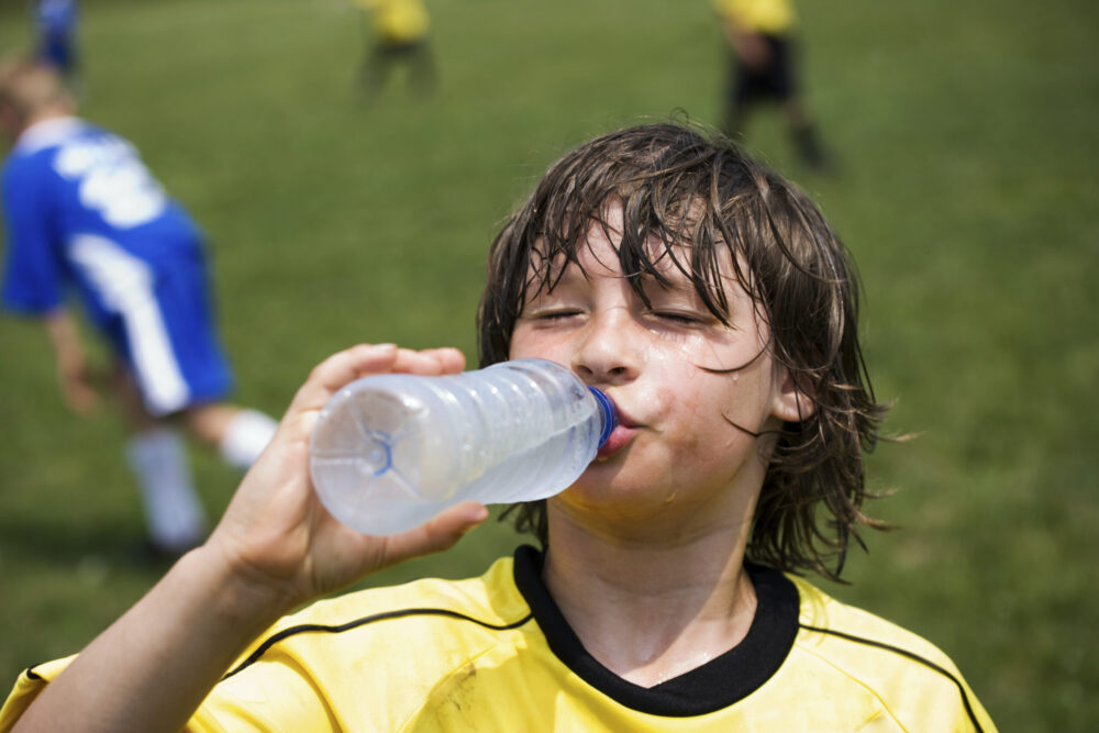 Kind drinkt water op sportveld